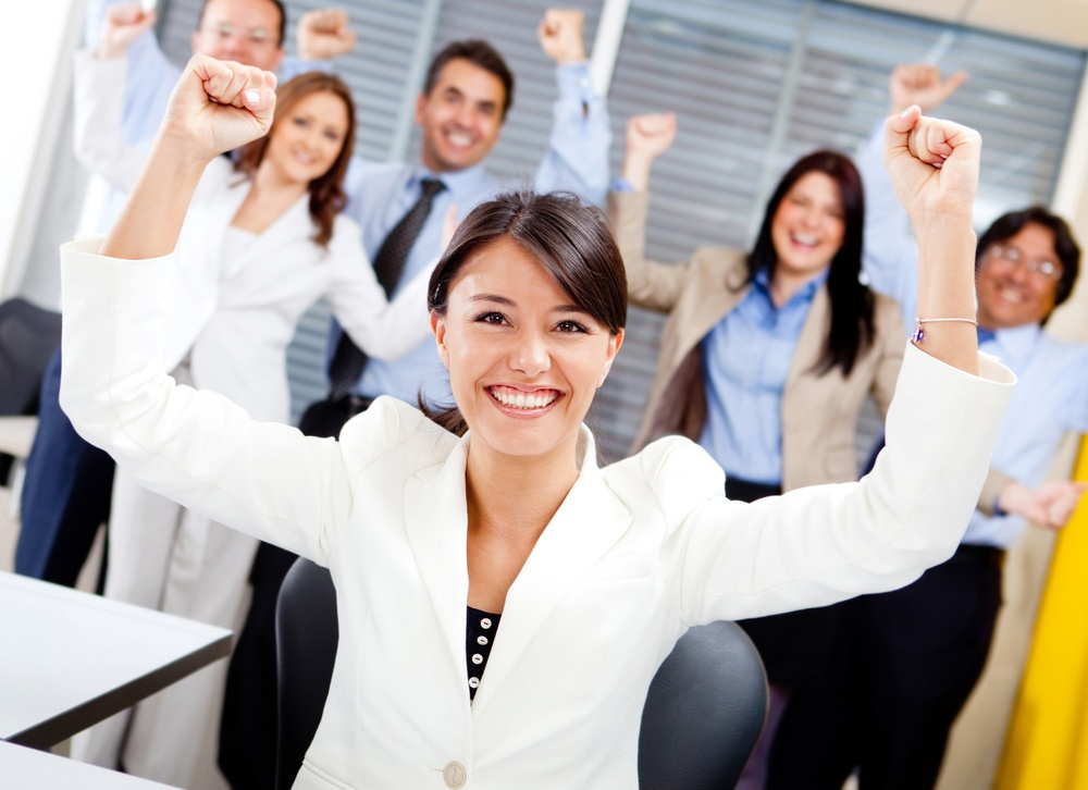 Business woman with arms up leading a successful team