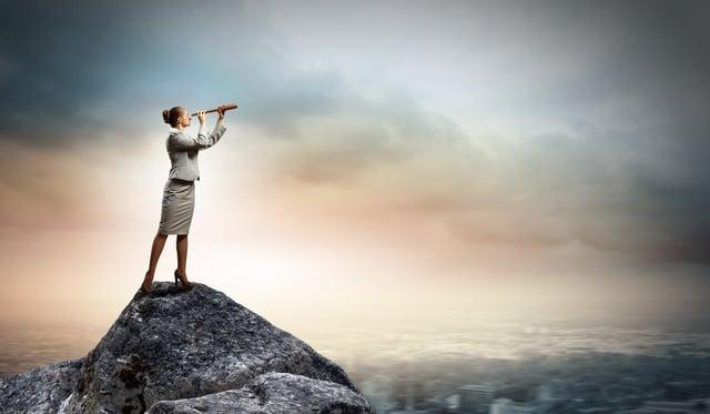 Businesswoman looking in telescope standing atop of rock