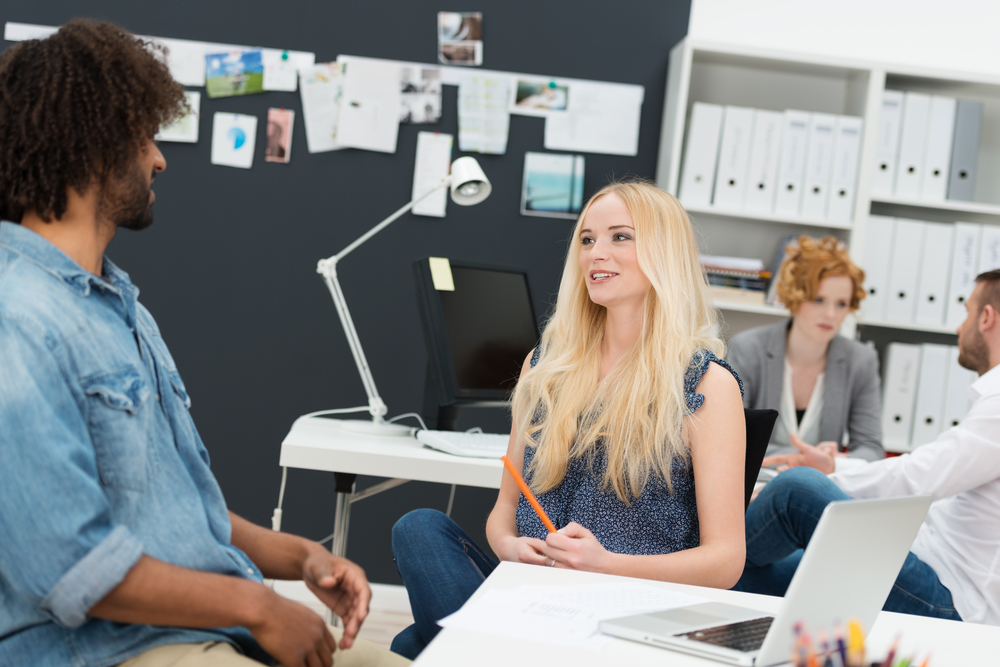 Two young businesspeople in a busy office sitting chatting with a beautiful young blond woman and young African American male in the foreground and colleagues working behind-1