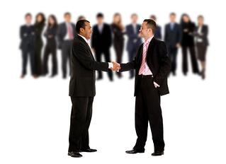 business men shaking hands with their teams behind them